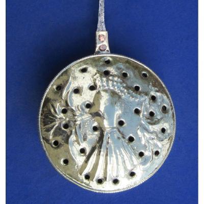 Bassinoire en laiton. Décor buste à large collier. XVIIe s.