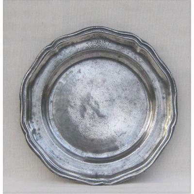 Assiette ronde, en étain, à bord festonné et mouluré. Milieu XVIIIe s.