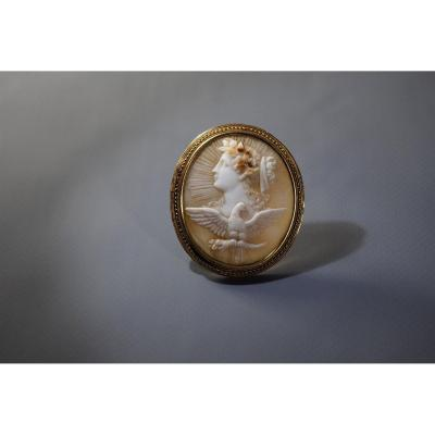 """Cameo brooch &quot;Geba, the young goddess&quot;<br /> Cameo (carved shell), gold. Stamps. Initials of the master on the back of the shell. France, end of the 19th century.<br /> Dimensions: height 5 cm, width 4.6 cm.<br /> Weight: 13,35 grams.<br /> Excellent condition, antique underlining; the closure has a safety mechanism.<br /> The cameo represents the image of Hebe, the Greek goddess of youth, in a crown of roses and with an eagle, which is one of her three attributes (with a jug and a bowl).<br /> Hebe&#39;s counterpart in Roman mythology is the goddess Juventa, who personified the eternal youth of Rome.<br /> For more information,<br /> <a href=""""https://antik-france.fr/en/"""">please visit our website by clicking here: www.antik-france.fr</a><br /> Item 4754"""
