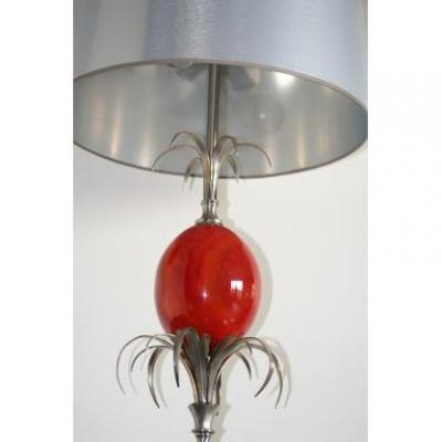 Lamp signed by the Maison CHARLES with three lights, the was in brushed satin metal and shiny parts, decorated in its center with an egg in imitation of orange-red marble, supported and surmounted by palm leaves. Octagonal base. Metallic / silver shade.<br />