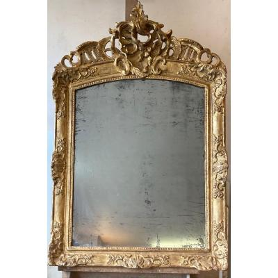 Sculpted and gilded wooden mirror from the 18th century Regency&nbsp;<br /> The curved pediment richly sculpted with a shell perforated over the entire width and surrounded by foliage scrolls.<br /> Exterior frame with rich ornamentation of lateral shells with florets.&nbsp;<br /> Corners decorated with spandrels with foliage and flowers.<br /> Gold leaf gilding in good condition.&nbsp;&nbsp;Original mirror.&nbsp;&nbsp;Parisian work<br /> Dimensions: Height (overall): 120 cm . Width: 80&nbsp;<br /> <br /> Price: 2800&euro;&nbsp;<br /> <br /> DELIVERY: Free and by hand for Paris and the Paris Region.&nbsp;For shipments to Province and other destinations, please contact us for a shipping quote, by mail or other shipping services.<br /> <br /> We pay special attention to the packaging of our items, to guarantee them maximum protection during their