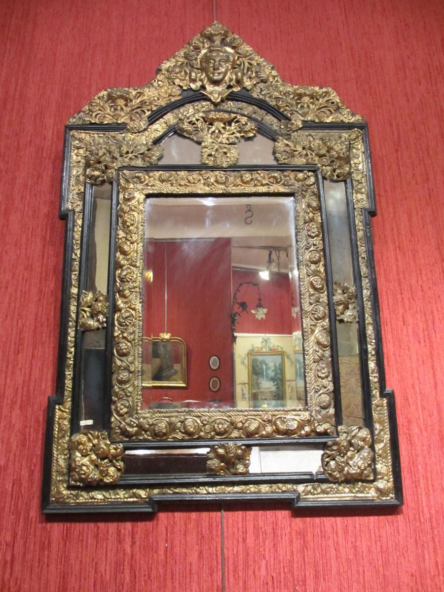 miroir en bois noir et laiton repoussé.