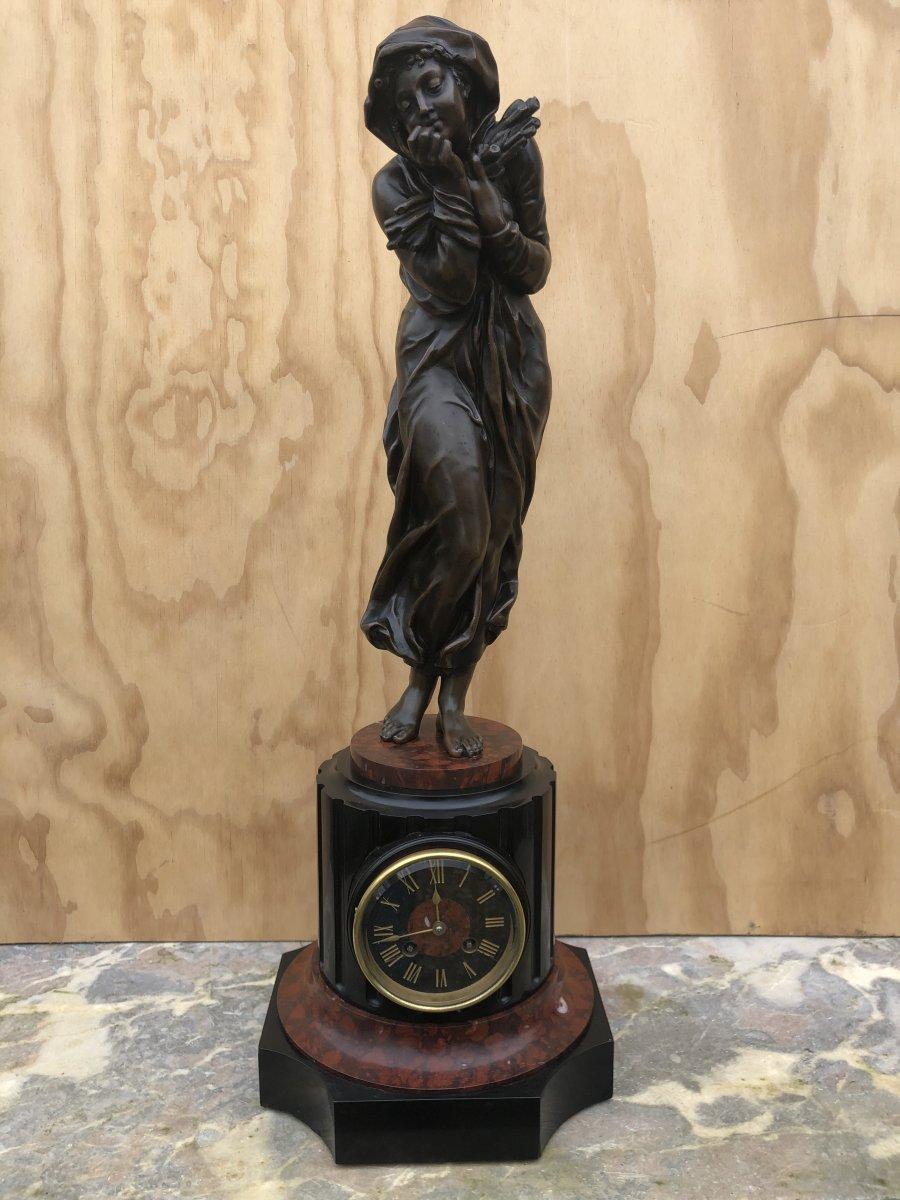 Pendule surmontée d'une femme en bronze soufflant dans ses mains pour se réchauffer