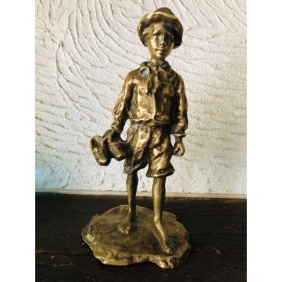 Bronze représentant un jeune garçon portant ses sabots à la main
