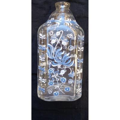 Très ancienne bouteille soufflée, peinte de motifs floraux bleus, blancs et noirs.