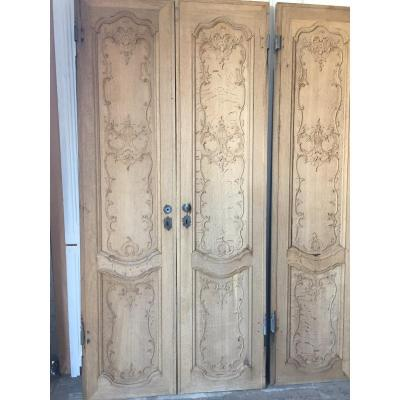 Set of three pair of finely crafted double-sided blond oak doors two scalloped reserves with rococo<br />