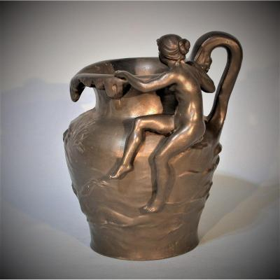 <strong>By Charles PERRON (1862-1934)<br /> <br /> VASE with pewter handle with dark patina with low relief decoration of two bathers and a grotesque mask; a naked young woman seated observes the inside of the collar.<br /> Signature of the artist and unidentified &ldquo;au coq&rdquo; foundry mark.<br /> Height: 19 cm.<br /> PARIS, circa 1900/1910 </strong><br /> <br /> Bibliography: &quot;Etains 1900&quot; by Philippe Dahhan<br /> In very good condition, complete with its small interior zinc tray<br /> <br /> *******************************************************************<br /> <strong>Website: http: / /www.commenchal-expert-etains.com </strong><br /> <br /> ******************************************************************<br /> <br /> PAYMENT<br /> <br /> - By French check payable to COMMENCHAL Jean-Claude<br /> - By bank transfer payable to COMMENCHAL Jean-Claude<br /> IBAN: FR7630027160990002011940139<br /> BIC: CMCIFRPP<br /> - By Paypal transfer to jc.commenchal@orange.fr An additional cost of 3 \% TTC of the price indicated will be invoiced to compensate for the fees charged by this banking operator<br /> <br /> GARANTIE<br /> <br /> Jean-Cl aude COMMENCHAL, expert specialist in pewter from all ages, guarantees the authenticity of the object described above. A detailed descriptive invoice including a photograph will be given to the purchaser on request.<br /> <br /> SHIPPING<br /> <br /> Sent to France by &quot;Colissimo&quot; followed within a maximum of 48 hours. With recommendation and insurance on request. Postal transport is offered to mainland France.<br /> Sent to the whole world by &quot;Colissimo&quot; recommended. With insurance on request. To know the shipping costs to Europe or the whole world, click on &quot;Buy online&quot; and select your country, or contact me by email.<br /> <br /> ASK A QUESTION<br /> <br /> French-speaking buyers: by phone or email.<br /> Non-French speaking buyers: exclusively by email.<br /> <br /> ******************