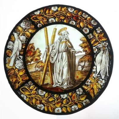 Stained glass window in medallion representing Saint Andrew with border decorated with birds, flowers and foliage. Glass painted with enamel and grisaille set with lead. To report a restoration in a border.<br /> In the style of the 15th century, early 20th century period<br /> Dimensions: Medallion diameter without border: 20 cm<br /> <br /> <em><strong>Saint Andrew</strong><br /> Andr&eacute;, whose first name in Greek means virile, courageous, is the brother of Simon Peter (Saint Peter). They were born in B&eacute;thsa&iuml;de, where they worked as a fisherman.<br /> Andrew, a disciple of Saint John the Baptist, followed Christ when his master pointed him out, saying &quot;Here is the Lamb of God. &quot;<br /> <br /> One day, while Andrew and Simon Peter were fishing in Lake Tiberias, Christ came and said to them &quot;Follow me and I will make you fishers of men.&quot; From that day on, they accompanied Jesus during all his years of Prediction.<br /> <br /> But in Patras, the current Patra in Greece, the proconsul Egeatus, whose family he had converted, had him tortured, then tied to an X-shaped cross. During the two days that his ordeal lasted, he continued to preach, so well that the moved crowd demanded that he be delivered, but the executioners, in spite of Egeatus&#39; orders, could not detach him from the cross.<br /> <br /> Indeed, the Saint had begged the Lord to let him die on the Cross, undergoing the same torments as the latter. Suddenly a bright light enveloped him and when it dissipated he was dead as he had wished.<br /> <br /> Maximille, the wife of a senator from Patras collected his body and had it embalmed. His relics were later transported to Constantinople, then taken to Amalfi after the looting of Constantinople during the Fourth Crusade. His head, which arrived in Rome in 1462, was kept in St. Peter&#39;s Basilica, before being returned in 1964 by Paul VI to the Bishop of Patra as a sign of friendship with the Orthodox Church. Amalfi likewi