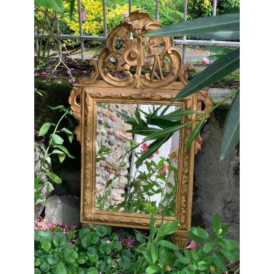 Carved and gilded wooden ice, 18th century.<br /> Mercury mirror.<br /> Ornate pediment with country decor (garden instruments, hat)<br /> Very good condition and the proportion is interesting.