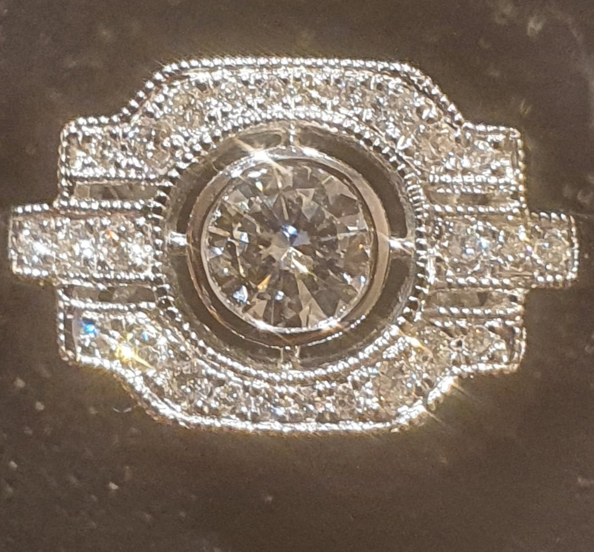 18ct White Gold Ring Set With A Diamond Surrounded By A Paving