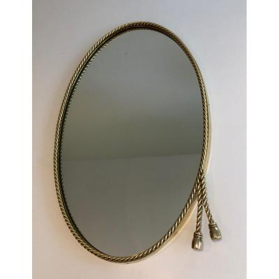 N The Style Of Maison Bagués. Oval Brass Mirror Surrounded By A Cord Decorated With 2 Pompoms.