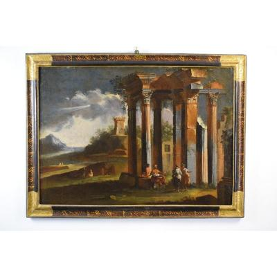 Venetian school of the beginning of the XVIII century<br /> <em>Architectural Capriccio with classic ruins and oriental figures</em><br /> <br /> Oil on canvas, cm 115 x 152 with frame; cm 98 x 136 canvas<br /> beginning of the 18th century<br /> <br /> The painting depicts a landscape composition of invention portraying on the right a ruined building, probably an ancient temple, on whose top have sprouted some plants. The fantasy ruins have columns and pilasters in composite Corinthian style; several fragments are lying on the ground. The scene is animated by lively figurines. Some dressed in the old style sit on the ruins, one is intent on smoking a long pipe. On their right they entertain two other characters with an oriental turban headdress. In the distance a verdant landscape with other small figures. A crenellated medieval tower is crumbled on a high ground. The landscape is lost towards a mountain, overlooked by a tormented sky, whose clouds filters a suggestive ray of light. The representation of a place of fantasy, also called architectural capriccio, was often in use among the Venetian painters and visionarists of the 18th century. The painter shows you a remarkable luministic virtuosity and manages to build a very pleasant work where the Rovinistic sensibility is closely linked to a theatrical and scenographic taste.<br /> For these characteristics and for the references to the Eastern world, the author is to be sought in the Venetian area of the beginning of the 18th century. The canvas manifests a derivation from themes present in the works of the Venetian (Italian) Marco Ricci, nephew of the great painter Sebastiano, with whom he collaborated repeatedly. Very inclined to the landscape theme, Marco Ricci preferred it and soon turned, recording influences from Titian, Tempesta, J. Eismann, with luminous compositions and rich of atmospheric effects. The influence of Salvator Rosa and Alessandro Magnasco, who inspired him and from whom drew the technique 