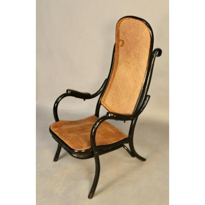 Curved wood and cane resting armchair, Thonet style. It is equipped with a mechanism that operates under the arms of the chair, allowing the footrest to be deployed. Very rare model. Cannage in perfect condition.
