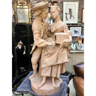 Large Terracotta Sculpture Representing A Young Couple Releasing A Bird From Her Cage.
