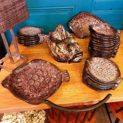 Exceptional bouillabaisse set by Marius GIUGE (1909-1980) in Vallauris, in the shape of a fish, in glazed earthenware with brown slip composed of<br /> 13 deep plates 24 cm<br /> 13 flat plates 26 cm<br /> 1 oval dish 42 cm<br /> 1 round dish 46 cm<br /> 1 fish-shaped soup tureen 48 cm<br /> 1 gravy boat 27 cm<br /> Delivery possible, estimate on request.<br /> You can follow the store on Instagram: Lesbillesdelagamine