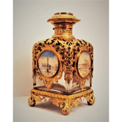 Rare crystal perfume bottle resting on four ball feet, embellished with a carved and gilded bronze lace, adorned with five miniatures inset on ivory all sides and cap representing various monuments of Paris.<br /> Napoleon III period<br /> dimensions: height 12 cm