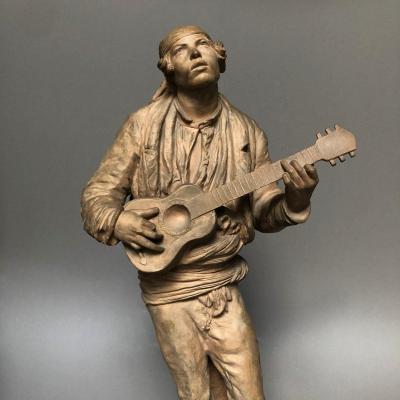 SÈVRES: Sculpture en terre cuite, jeune homme à la guitare, signé V. OMS