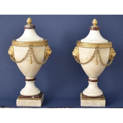 Pair of covered urn-shaped vases. White and morello cherry marble. They are garnished with gilded and chased bronze, representing lions and chains muzzles. The plug is shaped like a pine cone. Original gilding. Louis XVI period.