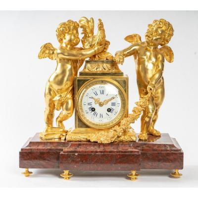 <br /> Important Louis XVI Style mantel clock in antique red marble, chiseled and gilded bronze with an allegorical subject of &quot;The rewarded study&quot; or &quot;The Awakening to Knowledge&quot;. Parisian work of the Second half of the 19th century, after a model created around 1775-1780 by the bronzier-chaser Robert Osmont. Imbued with neoclassical Louis XVI aesthetics, this small watchmaking monument on which gilded bronze and antique red marble are harmoniously orchestrated, is organized around a quadrangular terminal encasing the movement fitted with a large white enamelled dial surrounded by pearls, of rais-de-coeur. Surrounded by an opulent banded laurel torus, ornate against a backdrop of guilloche panels with acanthus florets and fluting, it is flanked by two superb allegorical figures of Cherubim modeled with jubilation. Nimbly perched on voluminous folios -attributes of Knowledge- bordering a rolled parchment -evocation of the Study-, one encloses a frigid Rooster-symbol of Vigilance, of diurnal activity-proudly erect wings spread on the covering of the clock. Slightly leaning on it, the second dreamer lets, in a graceful attitude, bend a heavy flowered garland - an evocation of sweet gratuities, of honors - whose spring foliage spreads out on the terrace. The entire composition rests on a rectangular molded base in so-called Antique red marble with a central projection carried by six spinning-top feet ringed with pearls. The formal skill of this timepiece can be found in the creations initiated in the last third of the 18th century by brilliant Parisian master bronzers or sculptor-chasers such as Robert Osmont (1711-1789) or Jean-Louis Prieur (1732- 1795), - &quot;major figures in the decorative arts of French Neoclassicism&quot;. Thus, it shares with the models of their famous clocks said to subject besides the scale, the architectural composition, the chromatic elegance, the ornamental sobriety, its pleasant iconography favoring the childish motif 