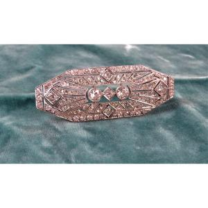 Beautiful hexagonal-shaped plate brooch in platinum and openwork grey gold, serrated with diamond roses and half-cut diamonds, two of which weigh approximately 0.80 ct each and five others weighing between 0.30 and 0.50 ct.<br /> Beautiful contrast between diamond roses and round diamonds.<br /> French work around 1920-25.<br /> Length: 7.5 cm<br /> Width: 3 cm<br /> Weight: 18,6 gr