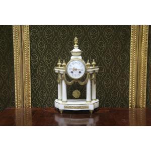 Pendule de forme portique en marbre blanc et bronze doré .