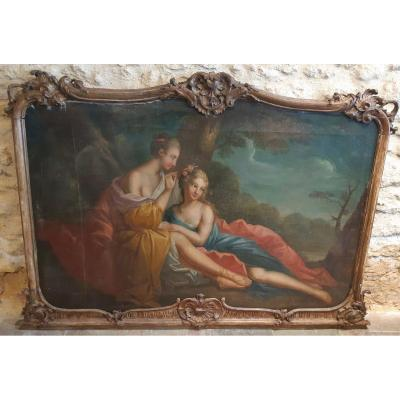 This large oil on canvas is the work of a French School of the late eighteenth, early nineteenth. She represents two languid young women, indulging in small pleasures and rest. Both dressed with long colored loose clothes left voluntarily to discover the skin of a shoulder, legs or the birth of breasts, they appear as very sensual and very complicit. One of them, lascivious, is lying barefoot on the knee of the other woman who adorns her hairstyle with small flowers. Her long blond hair falls on her bare shoulders and her bright eyes, on the side, seems to tell us that she thinks of a gallant encounter. The other woman, in profile, very delicate in the gestures she has with the laying of flowers, is also sensual by her bare neck and shoulder and by the richness of the fabrics of the clothes. His lifted hair uncovers his neck, his feet are wearing sandals. They are outside, in a nature bounded by a row of trees with a light body of water and a dark sky. The tree trunk behind them interposes in their duet and gives a certain strength. This oil on canvas is in a beautiful frame of carved woodwork. There are traces probably due to an old frame and enlargement of the canvas. Some gaps, old lining. Could be a door top. Dimensions without frame: L 136,5 cm / H 91 cm Dimensions with frame maximum: L 157 cm / H 109 cm