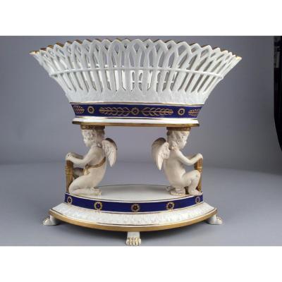 Coupe Ajourée En Porcelaine Supportée Par Deux Angelots De Style Empire, Marque Apocryphe.