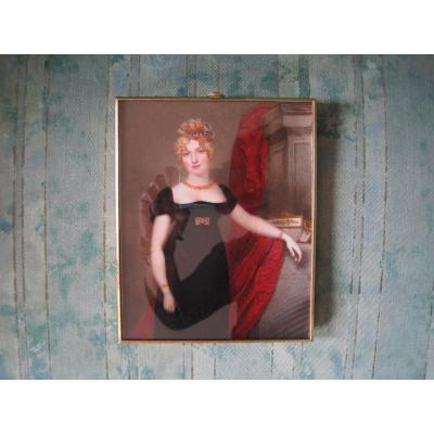 Samuel John Stump, portrait miniature of a lady with a strong face resemblance to a print of Sarah Smith, Mrs. Bartley (1783-1850), with blond hair,  wearing a red dress and jewellery, standing before a column draped with red cloth, beside a white casket.  Stump was famous for his portraits of celebrities and in this portrait he refers to the actress' role as Portia in The Merchant of Venice.