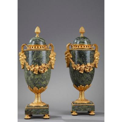 PAIR OF CASSOLETTES Louis XVI neoclassical style. In green marble with gilt bronze frame with motifs of heads of fauns, garlands of flowers and fruits. The catch of the cover presents a seed in gilded bronze.<br />