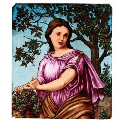 This stained glass was realized on a clear glass&nbsp; painted with &quot;grisaille&quot; and colored enamels and then fired.<br /> This painting represents autumn, a woman is holding a basket with grapes.<br /> First quarter of the 20th century.