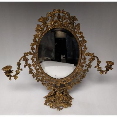 <br /> Very pretty bronze psyche, richly sculpted and decorated with vine and grape leaves. On the base, shells, swans, reeds. The glass of the oval mirror is bevelled and tilting and framed by 2 candle holders. Nineteenth century. Good general condition (a few small bites on the mirror and torn fabric at the back). Dimensions: height: 53 cm; width: 57 cm with the candle holders (36 cm without); Mirror: 24 cm x 30 cm. deep<br /> &nbsp;