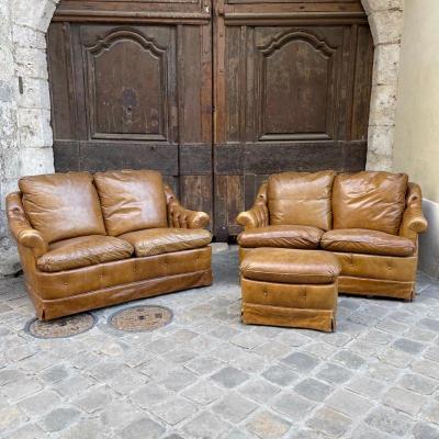 Paire de canapés en cuir et ottoman