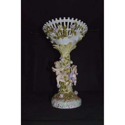 Beautiful porcelain centerpiece made in Germany, Three Cherubim on a column garnished with flowers, surmounted by an openwork cup strewn with flowers Small gaps (a few flower petals) not bad
