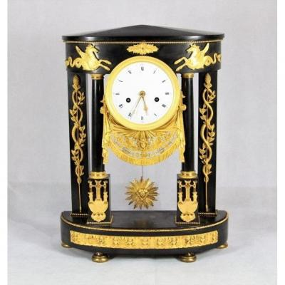 """Temple"" clock in black marble and finely chiseled and gilded bronze with plant motifs, intertwined branches and snakes and winged horses. The enamelled metal dial with Roman numeral hours, key and works perfectly Empire period."