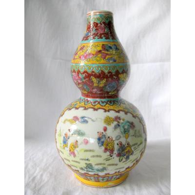 Vase gourde en porcelaine de Chine. Décor d'enfants jouant au ballon. Marque Qianlong