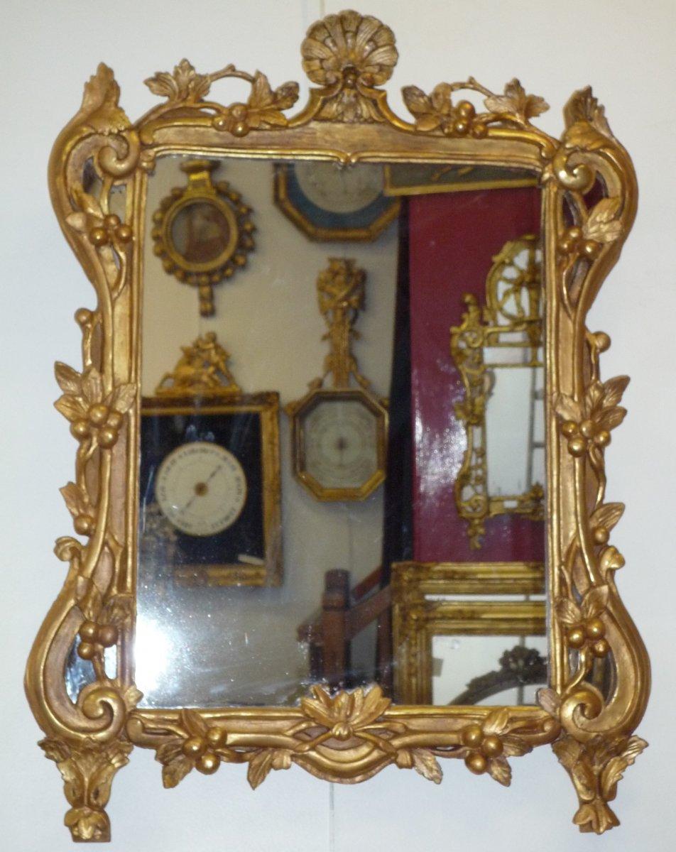 Miroir d'époque Louis XV en bois sculpté et doré à décor de feuillage et de fruits.