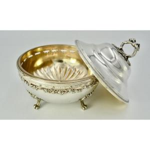 Round shaped covered sugar bowl in silver resting on four applique legs formed of acanthus leaves and finished in volutes. The half-spherical body flattened and pierced at the top is decorated with a garland of rose flowers and wrapped nets. The interior is in vermeil. The domed cover is outlined at the edge of a frieze of flowers and finished with a screw-on ring-shaped grip executed in cast and chiseled silver showing a ribboned bay stalk and its leaves.<br /> The receptacle is made of crystal, the bottom of which is cut in the shape of a star.<br /> 950/1000 silver, Minerva hallmarks<br /> Master Goldsmith: Paul Canaux &amp; Cie, 1892-1911<br /> Diameter: 13.7 cm<br /> Height: 14cm<br /> Weight without crystal: 424 gr
