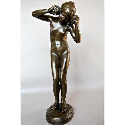 """Bronze statuette with brown-green patina, produced in the first part of the 20th century representing a girl wearing two conch shells in her ears to listen to """"Echo of the sea"""" title of the work signed on the base: L ALLIOT, numbering and mark of the founder Unis France. Some wear of seniority, good general condition. Lucien Charles Edouard ALLIOT was born in Paris (1877/1967) he learned sculpture with Barrias and Jules Coutant, he exhibited at the Salon des Artistes Français from 1896, among his many awards, he received a gold medal in 1920, he was appointed member of the jury from 1934 to 1939, his style, well anchored in the Art-Deco era, was produced mainly between the two wars."""