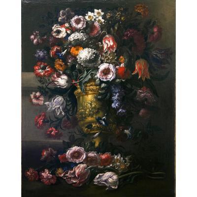 Superbe composition florale à l'intérieur d'un vase en relief en métal doré à motifs végétaux.