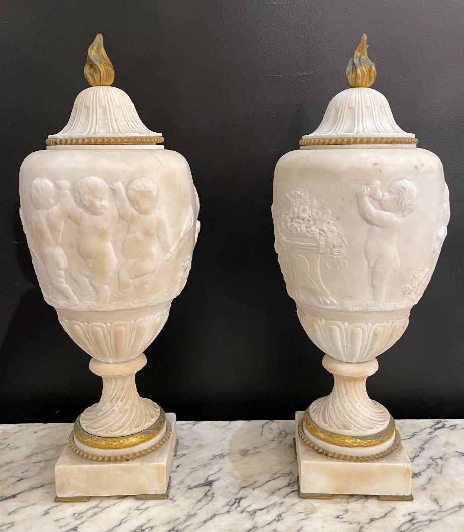 Paire De Vases Couverts En Marbre Et Bronze Doré - Décor d'Une Frise De Putti Jouant