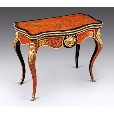 Game console table, all sides inlaid in counterpart with copper bottom and inlay of red tortoise with foliage, arabesque and floret motifs in the style of Charles Boulle; a beautiful ornamentation of chased and gilded bronze like: Bacchus mask, espagnolette with angel bust, laurel ingot molds and heart grapes without forgetting the leafy pads and the windings, amplifies the decor. The tray is articulated in the middle part in two equal sections then pivots laterally revealing in interior a vat in mahogany veneer. Once deployed horizontally, the two parts complement each other to obtain a square quadrilateral flat surface with multi-lobed contours. It is adorned at the periphery with a large sinuous cartouche of arabesques, scrolls and interlacing. A green game-carpet wraps its interior. The whole rests on a base with four arched feet punctuated by hooves in leafy loops. Parisian work Napoleon III. Very beautiful state of conservation parfectly original without uplifts or accidents, no restorations, only cleaning was mak.<br />