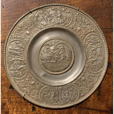 Small pewter dish decorated in relief or &#39;Paten&#39; from N&uuml;rnberg, Germany, 1st half of XVIIth century<br /> <br /> Religious thema dated 1619 in reserve representing at the center the Noah Thanksgiving, titled/captioned in German language &quot;NOE GIENG AUS DER ARCH GETR OSTFERDT 16-GOTT-19&quot;,<br /> and on the large edge four medallions depicting scenes from the life of Adam and Eve, driven out of Paradise, alternating with flowery vases.<br /> <br /> Several punches including one for the city of Nuremberg (top cartridge) and 2 other unidentified tin potter&#39;s punches, including an IVB mark surmounting 3 bell towers in an octagonal cartridge (bottom cartridge)<br /> <br /> Model from Paulus OHAM, who create this mould in 1619.<br /> <br /> Perfect condition, without any suspension hole like often, no fel/cut neither restoration<br /> Very nice patina<br /> <br /> Plaese check on my next proantic pages a similar Nurnberg pewter plate depicting the emperor Ferdinand II equestrian portrait, surrounded the&nbsp; Habsburgs dynasty Electors equestrian portraits.
