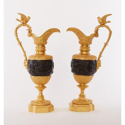These are a large and impressive pair of 19th century French ewers. The gilt bronze handles mounted with a satirical mask, scrolling handles topped with a pigeon, the beak decorated with grape vines and leaves. The middle patinated bronze body with classical scenes of cherubs. Below a gilt acanthus section, a grapevine wreath and a bronze base.<br /> French, circa 1880.