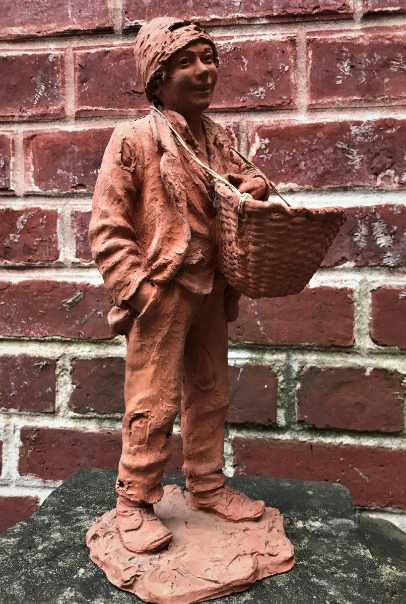 Sculpture en terre cuite : jeune homme en haillons portant un panier