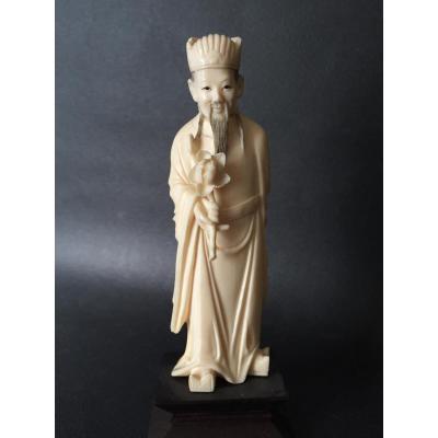 Okimono en ivoire, dignitaire tenant dans sa main une pivoine, Chine début XXe fin Qing