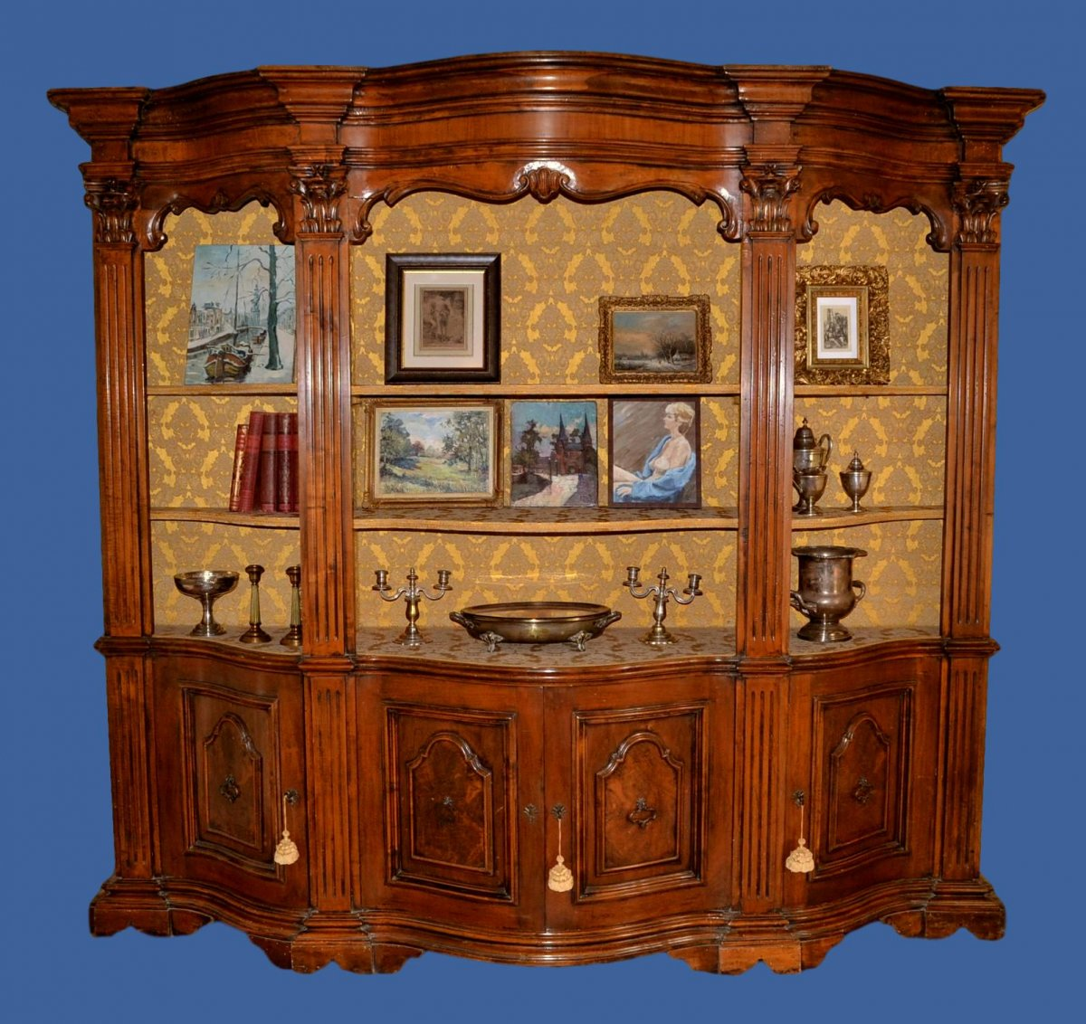 Large wooden sculptured natural wooden bookcase, four pillars; six shelves in facade covered, as well as funds, velvet of Genoa in very good condition. Opening with four doors in the lower part, closed by old locks, shelves inside. The assembly consists of three distinct parts assembled by lag bolts. Louis XV style, spectacular ensemble, circa 1950.<br /> <br /> Certificate of authenticity&nbsp;Height: 234 cm, width: 260 cm, depth: 60 cm.